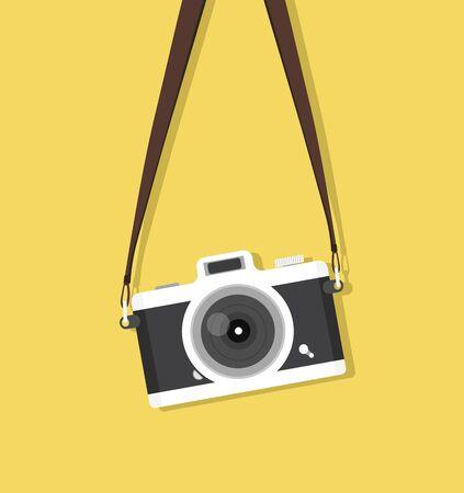 Appareil photo vintage suspendu avec sangle sur fond jaune