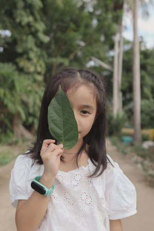 Sweet little girl outdoors and green leaf