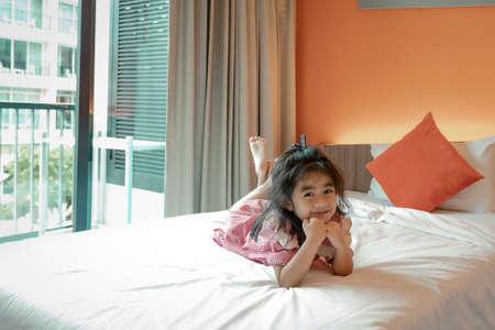 Cute little girl lying on bed