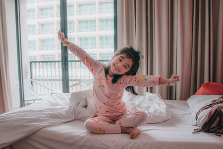 little girl wakes up in morning in bed