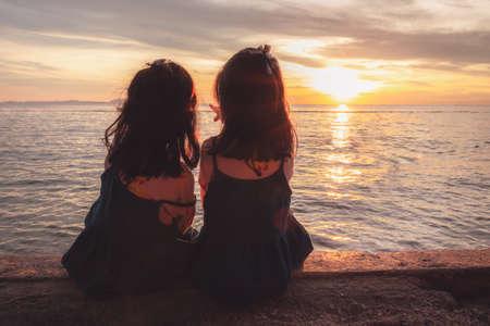 Silhouettes two little girl sit sunset beach Stok Fotoğraf