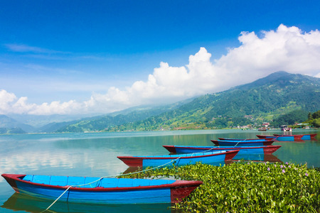 Beautiful landscape of Phewa Lake in Pokhara, Nepal. Background with colorful boats, beautiful blue sky, clouds and Himalaya mountains. Traveling Asia, Lifestyle vacations holiday concept.