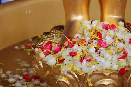 tunable: Bathing the Buddha, A Buddhist Thai is bathing a Buddha statue to gain merit Stock Photo