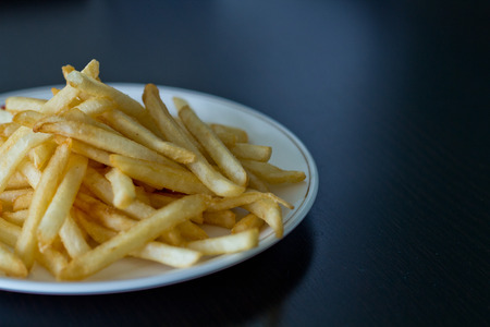 waxes: Potatoes fries on a little white paper bag