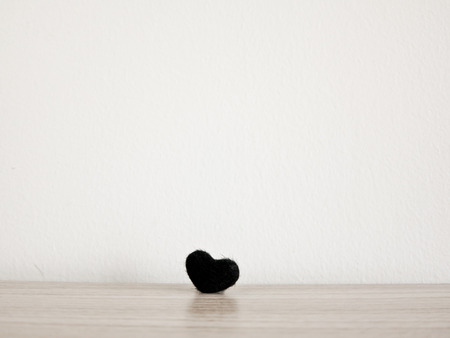 angel alone: black heart  On table wood background