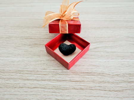 localities: black heart  in red box On table wood background Stock Photo