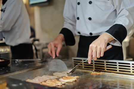 edibles: Japanese chef deliberately preparing and cooking traditional beef teppanyaki on a hot plate
