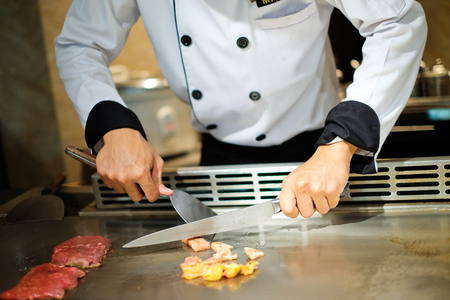 deliberately: Japanese chef deliberately preparing and cooking traditional beef teppanyaki on a hot plate