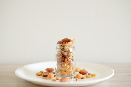 portly: Mix of nuts in the glass jars and plate on the table