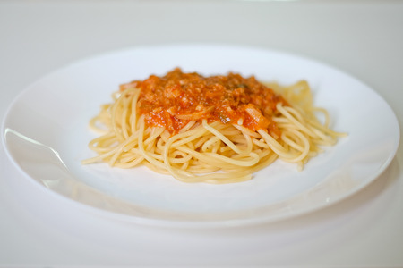 mee: Italian spaghetti topped with a tasty tomato and  beef sauce on white table Stock Photo