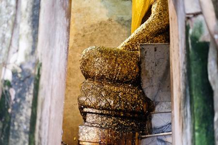 Ancient Buddha statue in old church which covered by banyan tree root at Wat Bang Kung at Amphawa in Thailand