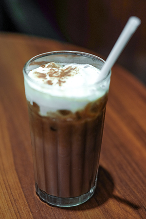 cocoa and milk foam on wooden table