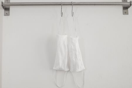 Two cotton cloth masks or hygiene masks are hanging on clothes hooks. Prevention covid-19 virus infection, Healthcare concept