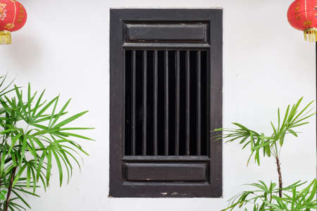 Closed window in Chinese style on white cement wall