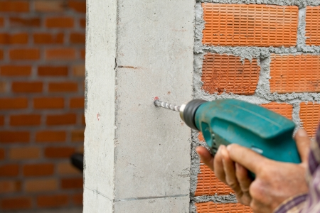 Drilling the wall with electric drill Stock Photo