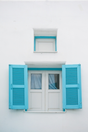 blue Windows on white wall with mini windows above it photo