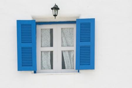blue windows and black lantern on white wall photo