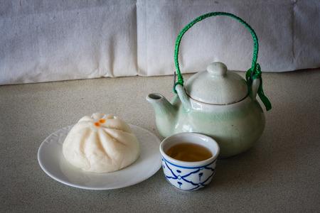 chinese tea pot: bodeg�n conjunto de chino tetera con bollo y taza en el calentamiento d�as