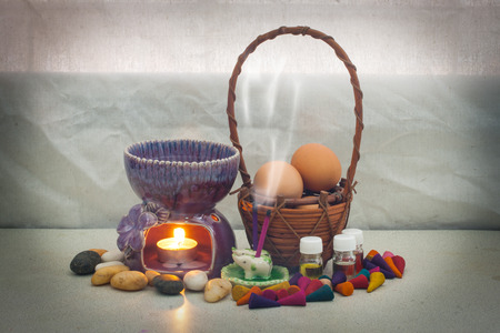 still life aroma set and Egg in rattan basket , aroma stove , joss stick , incense cone , aroma oil . concept relax photo