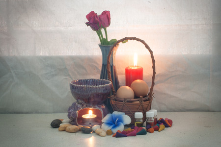 still life aroma set and Egg in rattan basket , aroma stove , joss stick , incense cone , aroma oil , red candle , pink rose . concept relax photo
