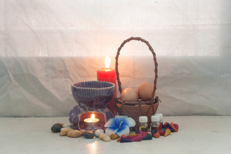 still life aroma set and Egg in rattan basket , aroma stove , joss stick , incense cone , aroma oil , red candle . concept relax photo