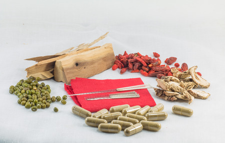acupuntura china: Chinese acupuncture needles on red cloth with chinese herb and herb capsule