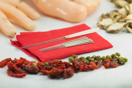 red cloth: close uo Chinese acupuncture needles on red cloth with meridian hand foot model with herb