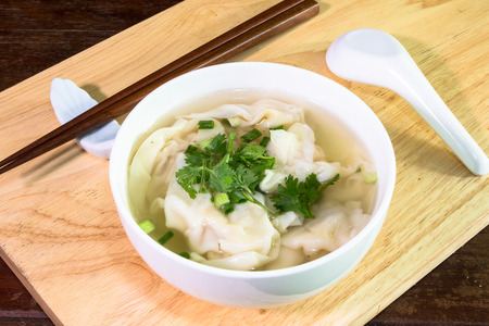 Wonton shrimp dumpling in clear soup with chopsticks