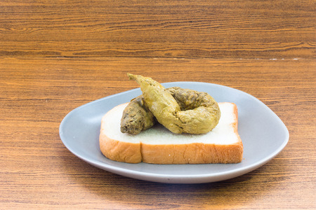 excrement: A poo on bread wooden background concept  Dirty Food Stock Photo