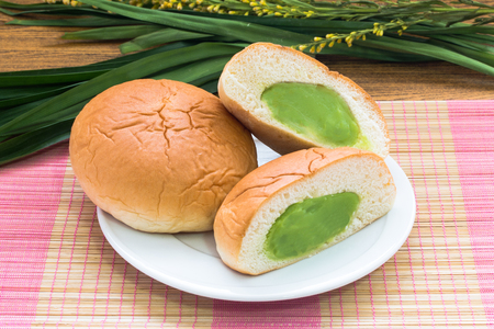pandan custard bun on bamboo mat  with pandan leaf still life style Stock Photo