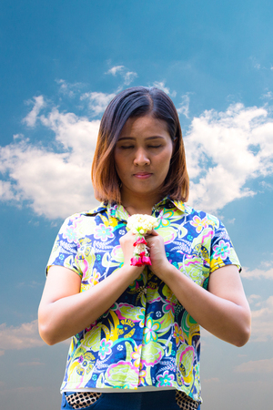Asian Woman pray with garland on blue sky background