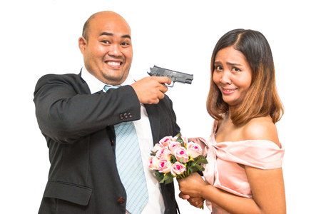 Asian man and woman in concept threaten with gun to married Stock Photo