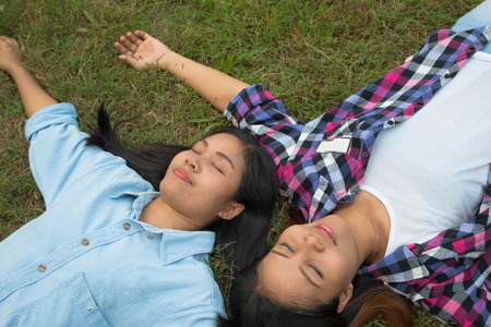 Twins asian woman sleep on grass concept happy in nature