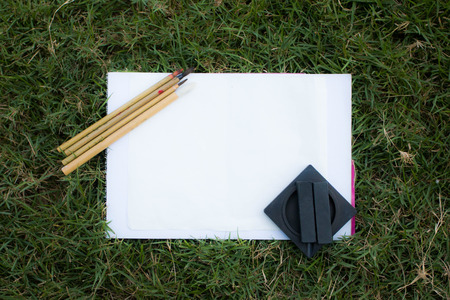Chinese paintbrush  inkstone and paper on grass concept relax nature Stock Photo