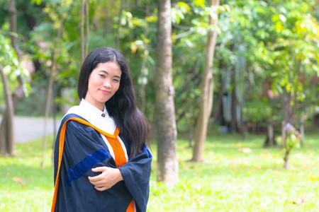 Asian woman in Graduate dress in park Stock Photo