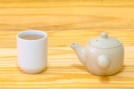 Tea pot and tea cup on wood background still life art Stock Photo