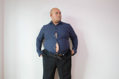 Asian fat man fasten small size of shirt on white Banque d'images