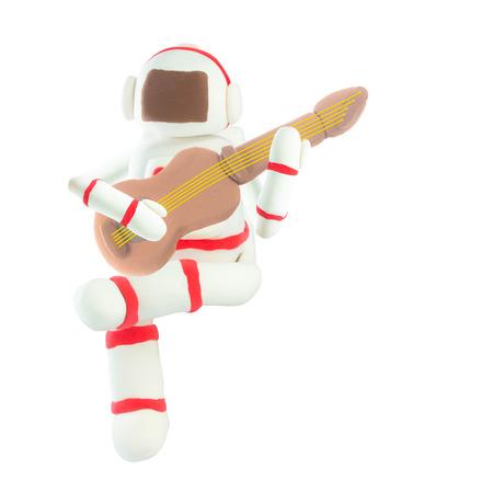Plasticine Astronaut play guitar on white Stockfoto
