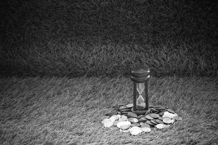 Money Coin and hourglass concept time is money on grass