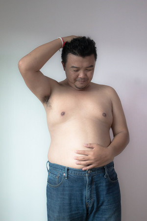 Asian fatman with big belly in worry action on white