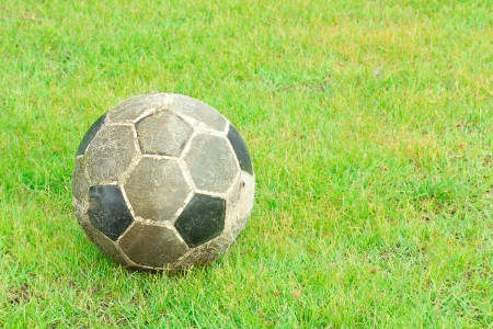 old soccer ball on green field