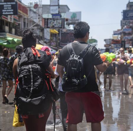Bangkok, Thailand - April 12, 2018 : Tourist happiness fighting with water gun on the first day of water festival in Khao San Road, Let's play with splash together in Songkran Festival Bangkok