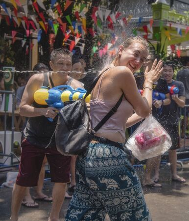 Bangkok, Thailand - April 13, 2018 : Tourist protect water gun shoot into her eyes on the second day of water festival in Khao San Road, Let's play with soaked together Songkran's day in Bangkok
