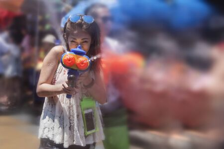 Bangkok, Thailand - April 13, 2018 : Tourist happiness fighting with water gun on the second day of water festival with blurred background in Khao San Road Editorial