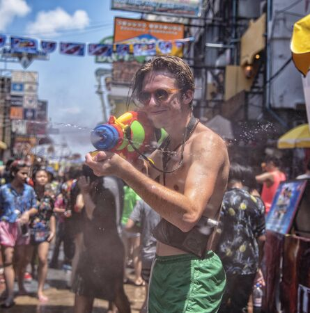 Bangkok, Thailand - April 13, 2018 : Tourist happiness fighting with water gun on the second day of water festival in Khao San Road, Let's play with soaked together on Songkran in Bangkok Editorial