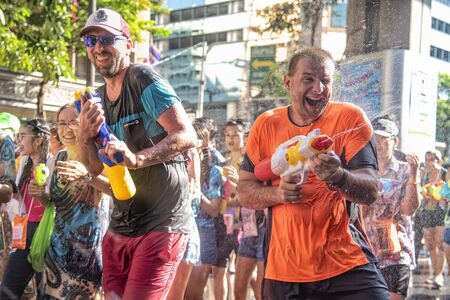 Bangkok, Thailand - April 13, 2018 : Tourist happiness fighting with water gun on the second day of water festival in Silom Road, Let's play with soaked together on Songkran%u2019s day in Bangkok