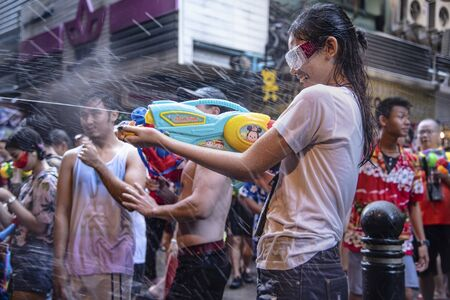 Bangkok, Thailand - April 13, 2018 : Tourist happiness fighting with water gun on the second day of water festival in Silom Road, Let's play with  soaked together on Songkran's day in Bangkok