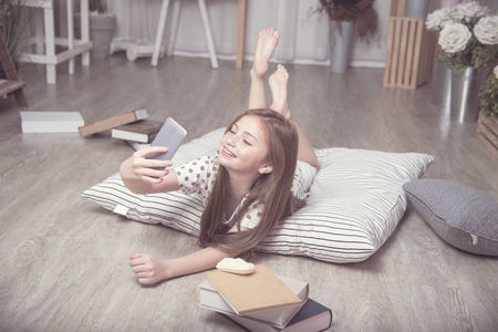 Adorable pretty girl take selfie herself in the living room, daughter on FaceTime with father on mobile