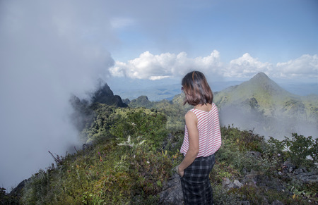 Tourists girl take a sight seeing foggy movement on the top of mountain at Doi Luang Chiang Dao, Chiang Mai, Thailand Stock Photo