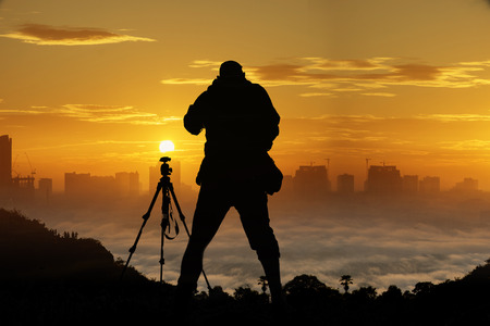 Trekking man take photo with the mist on the top of the mountain & vibrant color Bangkok city background (Retouch image) Stock Photo